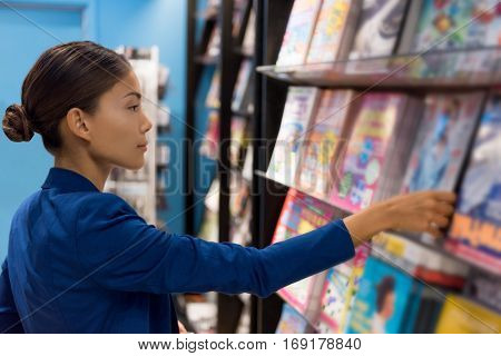 Businesswoman reading magazines at newsstand store of airport or train station. Asian woman shopping at bookstore.
