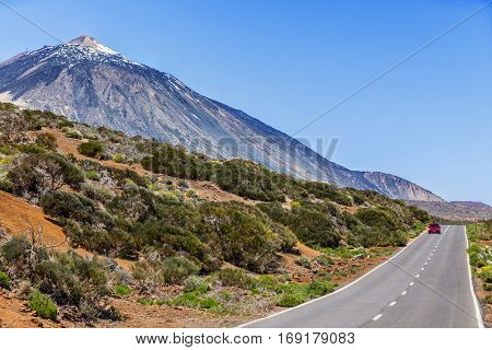 Red car driving on open highway near Teide volcano mountain summit, Tenerife, Canary islands. Freedom on holidays, road trip concept. Mountains in beautiful summer landscape.