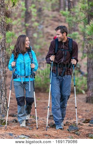 Happy couple hikers talking together on outdoor nature walk. Young multiracial people hiking outdoors in forest. Smiling Asian woman and Caucasian man.