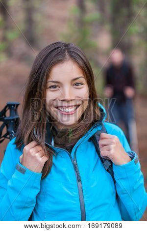 Happy Asian hiker girl in forest with backpack and hiking poles walking with group of friends. Healthy smile Chinese woman tourist.