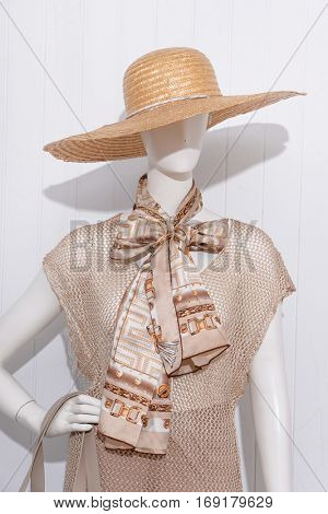 female sundress clothing with hat and scarf on mannequin-wooden background