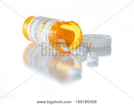 Non-Proprietary Medicine Prescription Bottle and Spilled Pills Isolated on a White Background. This label contains only fictitious information.