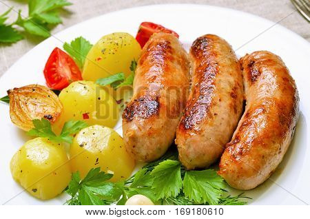 Grilled sausages and boiled potatoes on white plateclose up