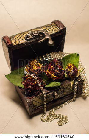 Wonderful trunk with dry roses and brilliant necklace.
