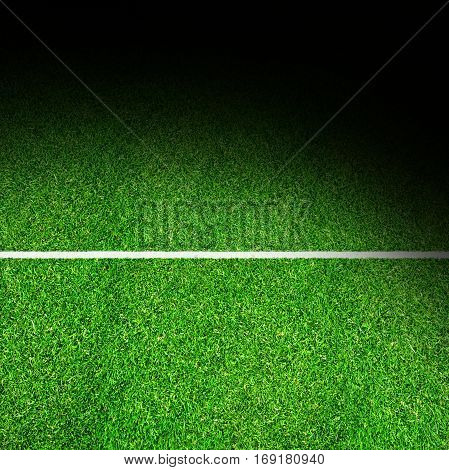 Deliberate spot lighting effect on sports field with marking and copy space. Background for any sports-theme art.