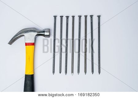 Hammer with few hammered and bended nails isolated on white background
