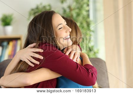Two affectionate friends or sisters embracing with love in the living room at home