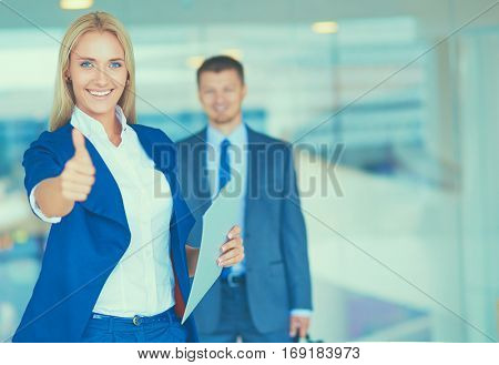 Successful young businesswoman showing ok , standing in office