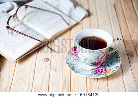 cup of coffee or tea on wooden table with open book and glasses
