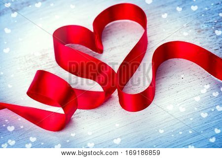Valentine Heart. Elegant Red heart shaped satin Ribbon Isolated on white wooden background. Valentine's Day design. Red silk ribbon curves Valentines art.
