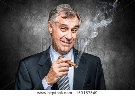 Confident senior businessman smoking a cigar