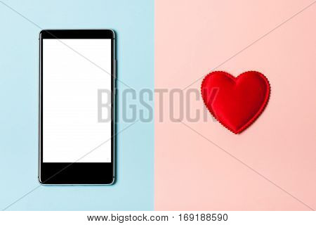 Smartphone on a blue background and heart on a pink background. The concept of love to your phone and technology love correspondence Valentine's Day surprise. Flat fly