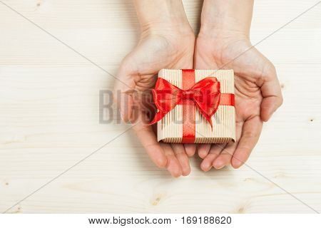 Two hands holding gift on a wooden background.Surprise your loved one. The concept of the day of St. Valentine's Mother's Day birthday New Year Christmas and other holidays. Flat fly.