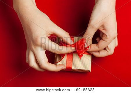 Hands packed gift in kraft box on a red background. The concept of St. Valentine's day weddings engagements Mother's Day birthday New Year Christmas holidays. Flat fly. Place for text