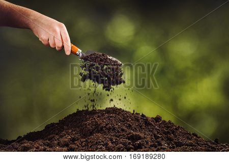 Hand pouring black soil with shovel on green bokeh background. Planting a small plant on a pile of soil or pouring soil during funeral. Gardening backdrop for advertising.