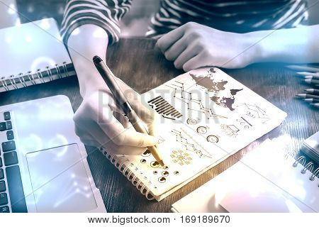Top view of hands srawing business charts and diagrams on spiral notepad placed on wooden desktpop with laptop and other items. Filtrered image