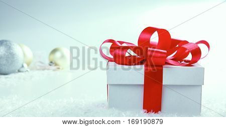 White gift box with red ribbon and bow.