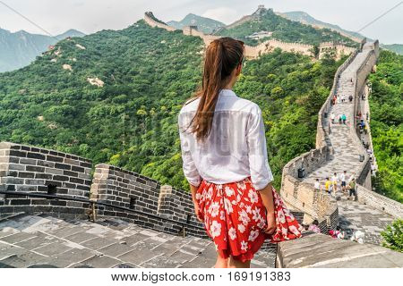 Young girl tourist from behind looking at view of Great Wall of China at famous Badaling tourism attraction during travel vacation in Beijing. Asia summer holidays. poster
