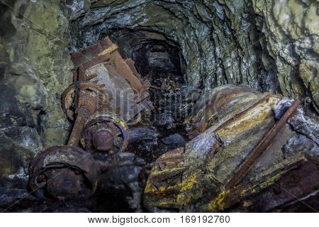 Collapse in tunnel of abandoned mine with rusty remnants of trolleys
