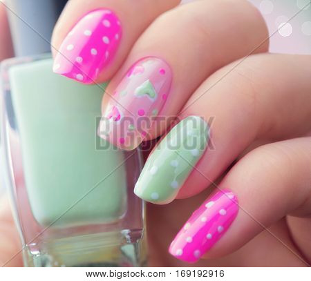 Valentine Nail art manicure. Valentine's Day Holiday style bright Manicure with painted hearts and polka dots. Bottle of Nail Polish. Beauty salon. Hand. Trendy Stylish Colorful Nails, Nailpolish.