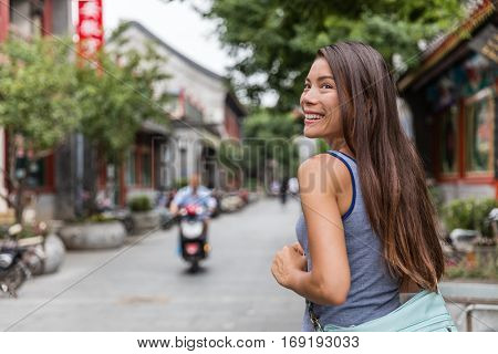 Happy asian tourist girl walking around chinese hutongs in Beijing coty, which are a type of narrow streets or alleys in typical neighborhoods with old houses. China summer travel tourism.