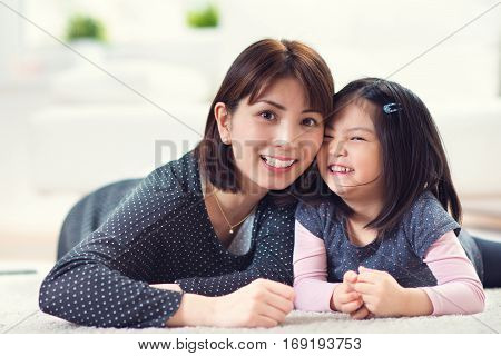 Pretty Happy Japanese Mother Play With Little Daughter At Home