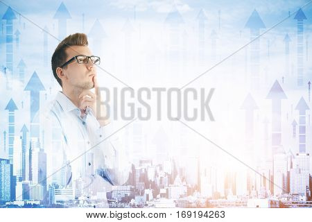 Attractive thoughtful businessman on abstract city with arrows background. He is thinking about success. Double exposure