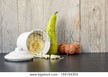 Blue cheese in white ceramic container, single pear and three walnuts on a black table with a weathered wood background