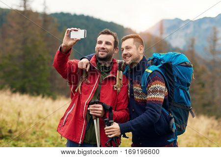 Two men in hiking gear standing outside taking a selfie with mountains behind them while out trekking in the wilderness