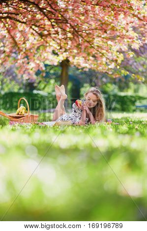 Beautiful Young Woman Having Picnic In Blooming Spring Park