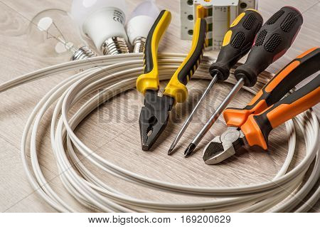 A set of tools electrician a coil of wire and equipment on a white background