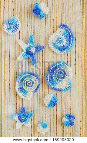 Marine background with cotton lace crochet craft elements: stars shells flowers made of soft acrylic like wool yarn. Crocheted creative small doilies. Decorative needlework marine design