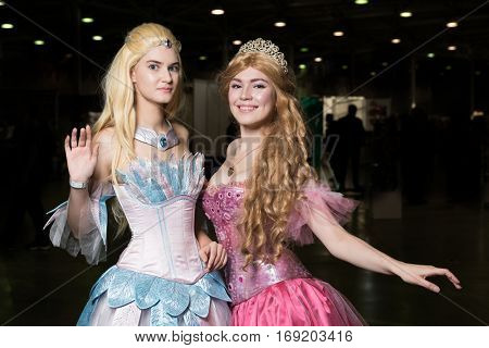 Two young woman cosplayer wearing beautiful dresses posing poster