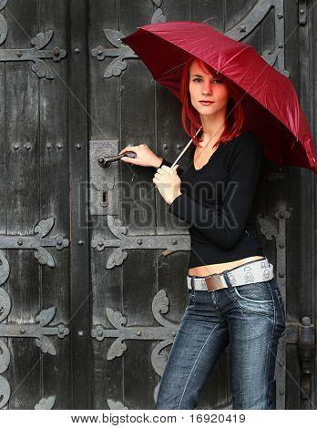 beautiful girl under rad umbrella