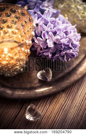 Beautiful wedding night decorations. Flowers and candles on wooden table, decor details, retro filtered.