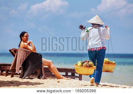 PHU QUOC, VIETNAM - APRIL 21, 2014: Vietnamese woman in traditional headdress, which protects from the sun offers fruits for sale to tourists at Long beach on Phu Quoc island, Vietnam.