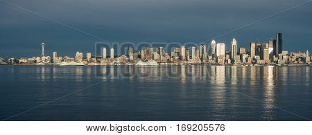 As the sun sets the buildings of the Seattle skyline are reflected in Elliott Bay.