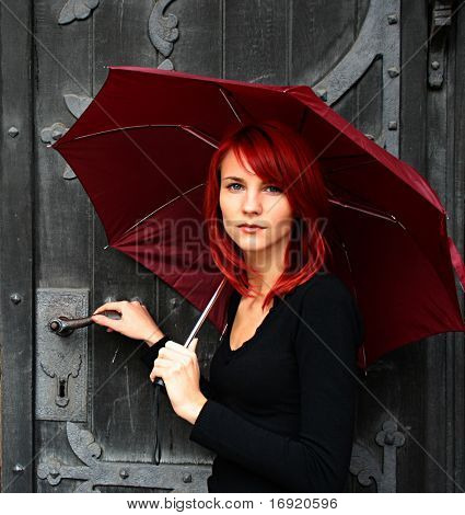 beautiful girl under red umbrella near the old door
