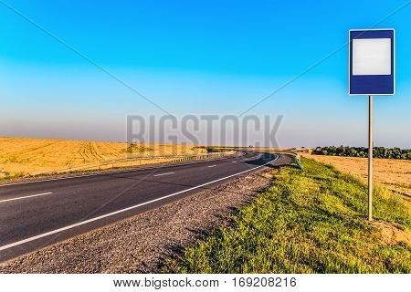 Countryside asphalt road with markings and empty information road sign to copy space. Rotate the road.