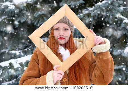 beautiful woman portrait on winter outdoor, look through wooden frame, snowy fir trees in forest, long red hair, wearing a sheepskin coat