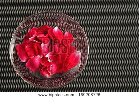 A glass filled with red rose petals