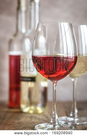 Glasses of rose and white wine on the wooden background