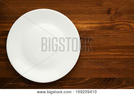 Plate On A Wooden Background. Plate Top View. Copy Space .white Plate