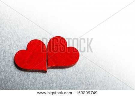 Two wooden red painted Valentine day hearts on metal background