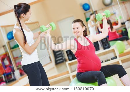 pregnant woman with instructor doing fitness ball exercise