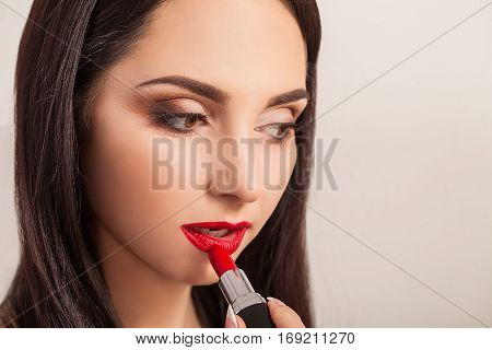 Beautiful woman paints lips with lipstick. Beautiful woman face. Makeup detail. Beauty girl with perfect skin.