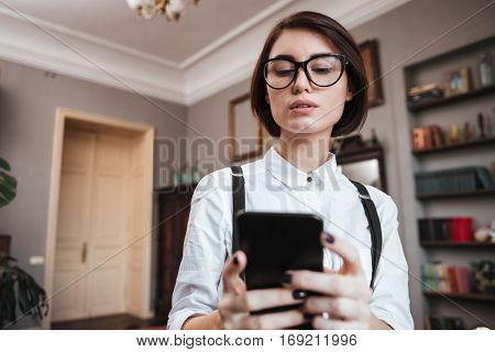 View from below of Authoress in glasses and white shirt using phone