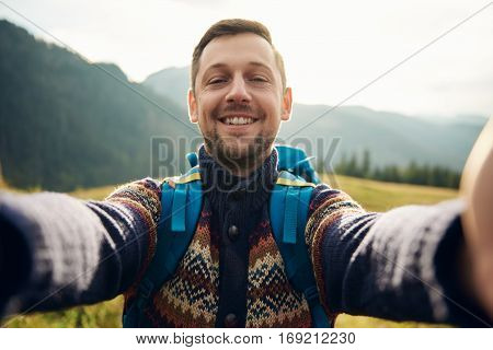 Young man in hiking gear standing outside taking a selfie with mountains behind him while out trekking in the wilderness