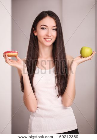 Diet. Woman Measuring Body Weight On Weighing Scale Holding Donut and apple. Sweets Are Unhealthy Junk Food. Dieting, Healthy Eating, Lifestyle. Weight Loss. Obesity.