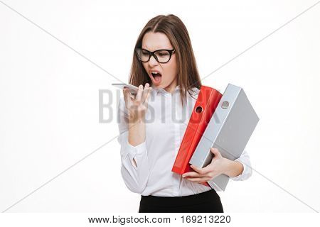 Annoyed hysterical young business woman in glasses shouting on cell phone and screaming over white background